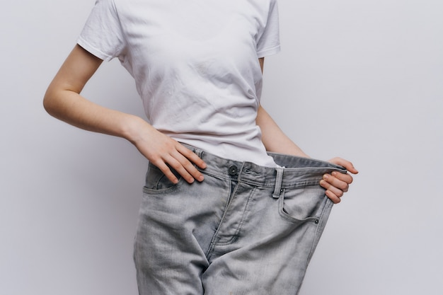 Bardzo szczupła kobieta schudła dużo na diecie i sporcie, pokazuje odchudzanie w starych dżinsach