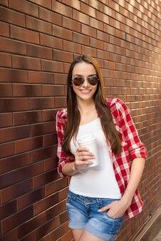 Bardzo uśmiechnięta kobieta trzyma filiżankę kawy