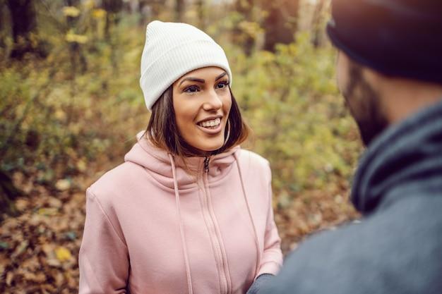 Bardzo uśmiechnięta młoda kobieta w odzieży sportowej, z czapką na głowie, stojąca na łonie natury, robiąc sobie przerwę i rozmawiając z przyjaciółką. fitness w przyrodzie na koncepcji zimnej pogody.