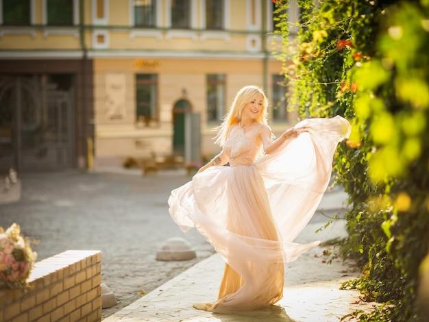 Bardzo uśmiechnięta młoda kobieta z długimi blond włosami w eleganckiej sukience latającego światła biegnącej wzdłuż ulicy