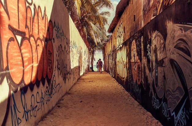 Bardzo wąska alejka pokryta graffiti prowadząca na plażę playa del carmen w meksyku, z dwoma osobami idącymi w kierunku wyjścia.