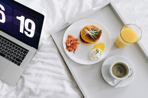 Bardzo wcześnie rano śniadanie z naleśnikami, łososiem, jajkiem, sokiem pomarańczowym i kawą
