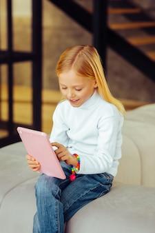 Bardzo zadowolony. uważne dziecko wyrażające pozytywne nastawienie podczas spędzania wolnego czasu w salonie
