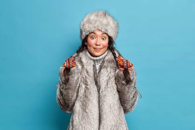 Bardzo zaskoczona młoda kobieta azji trzyma warkocze ubrane w odzież wierzchnią na białym tle nad niebieską ścianą. eskimoska w kapeluszu i płaszczu żyje w arktycznym miejscu