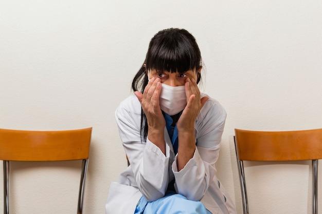 Bardzo zmęczona, płacząca i zamyślona pielęgniarka siedząca w poczekalni po zmianie w szpitalu.