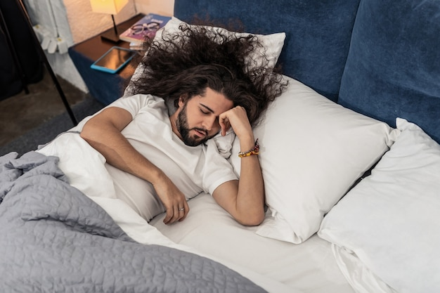 Bardzo zmęczony. miły długowłosy mężczyzna próbuje spać będąc bardzo zmęczonym