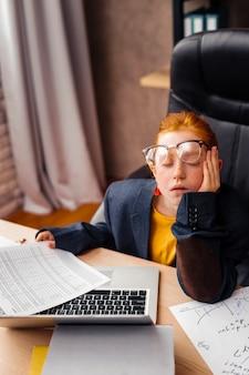 Bardzo zmęczony. przyjemna miła dziewczyna siedzi przy stole z zamkniętymi oczami podczas snu