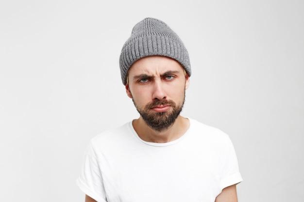Bardzo znudzony dorosły mężczyzna z brodą, wyglądający na zmęczonego i chorego