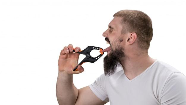 Bariera językowa, pogłoski, problemy z wyrażaniem koncepcji. mężczyzna z brodą przycisnął język dużym spinaczem do bielizny