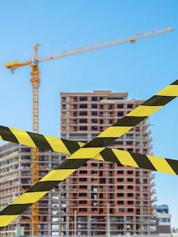 Barierowa taśma zakazowa na rozmazanym tle budynków w budowie i błękitnym niebie