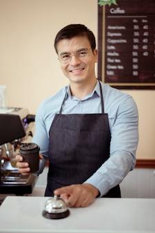 Barista bierze kubek gorącej kawy i piekarni do oferowania klientowi w kawiarni