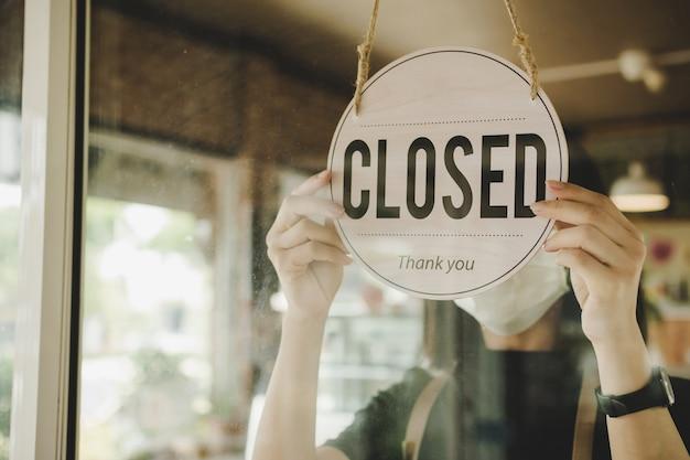 Barista, kobieta kelnerka nosząca maskę ochronną, obracająca się blisko tablicy znak na szklanych drzwiach w nowoczesnej kawiarni kawiarni, restauracji kawiarni, sklepie detalicznym, właściciela małej firmy, koncepcji żywności i napojów