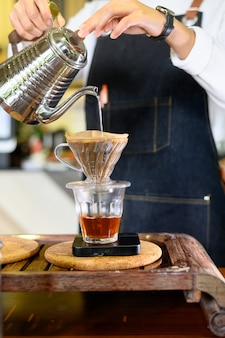 Barista kobiety dziewczyny gorąca woda przygotowywa filtrującą kawę