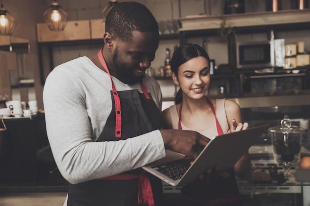 Barista mężczyzna i kobieta patrzeje laptop