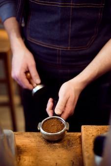 Barista naciska kawę mieloną za pomocą manipulacji w sklepie z kawą