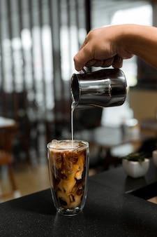 Barista nalewa kawę do szklanki