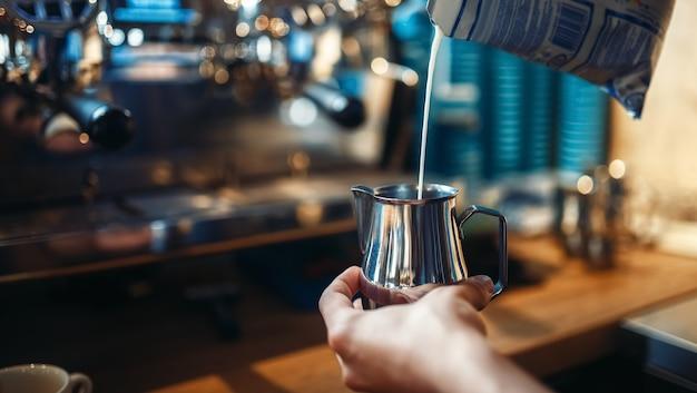 Barista nalewa śmietankę do filiżanki kawy