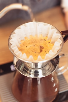Barista nalewa wodę na zmieloną kawę z filtrem