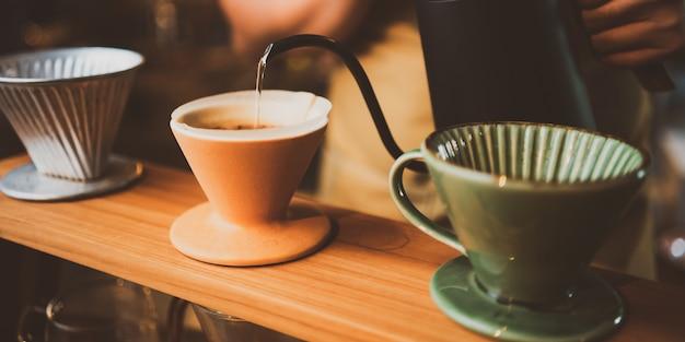 Barista parzy kroplówkę filtra kawy rano, napój napój o świeżym aromacie czarnego espresso, gorący napój w filiżance kawiarni, brązowa kofeina w tle sklepu barowego