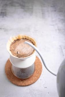 Barista polewał zmieloną kawę gorącą wodą.