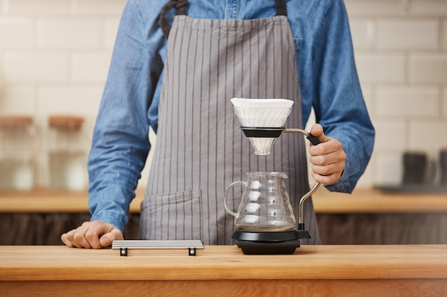 Barista przy kontuarze barowym ma zamiar zrobić kawę pouron.