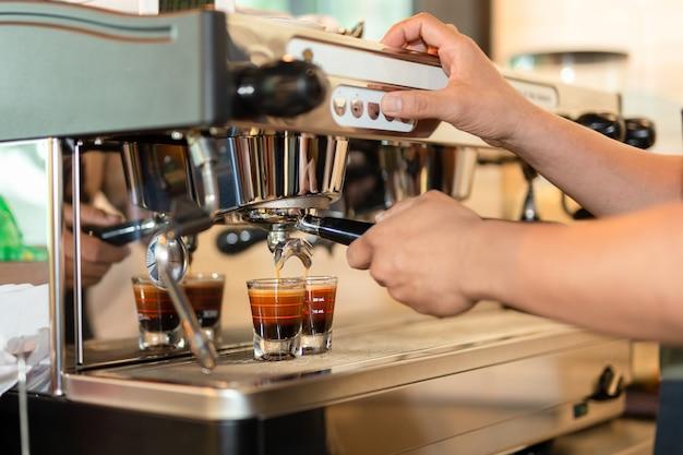 Barista przygotowuje kawę espresso zastrzelony z maszyny parzenia kawy