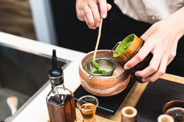 Barista przygotowuje napój zielonej herbaty