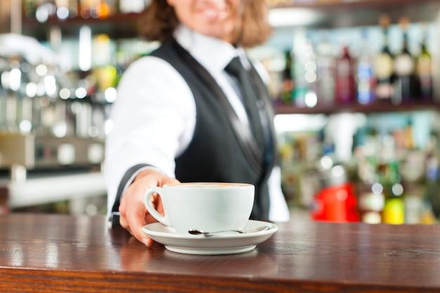Barista robi cappuccino w swoim sklepie z kawą