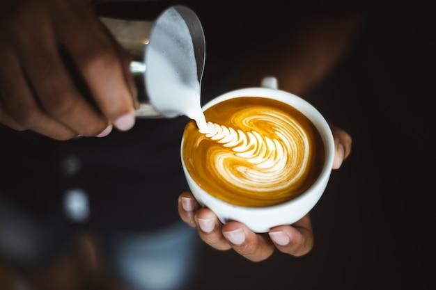 Barista robi filiżance kawy latte sztuka.