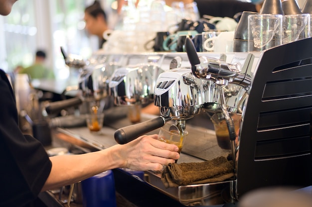 Barista robi filiżankę kawy przez ekspres do kawy w kawiarni