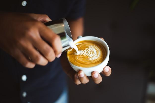 Barista robi filiżanki kawy latte sztuce w sklep z kawą.