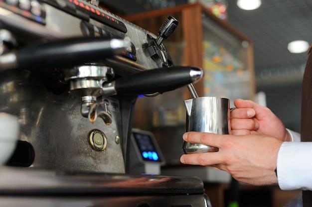 Barista robi kawę. przygotowanie mleka do cappuccino