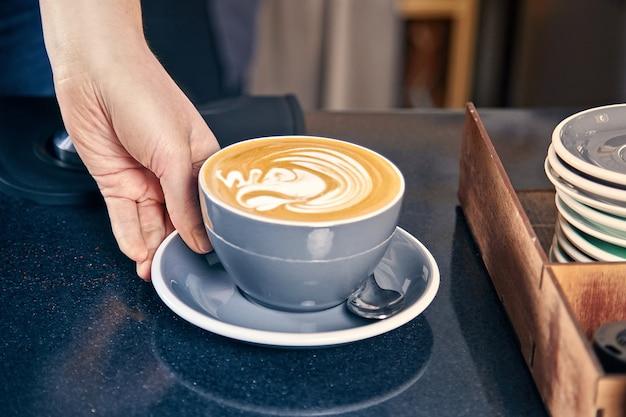 Barista serwująca kawę w kawiarni. kobieta daje latte lub cappuchino klientowi za kontuarem. restauracja coffee shop concept. stonowane zdjęcie. skopiuj miejsce świeżo parzona kawa