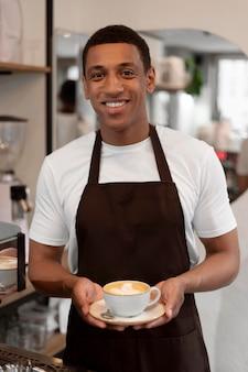 Barista średniego strzału trzymający filiżankę kawy