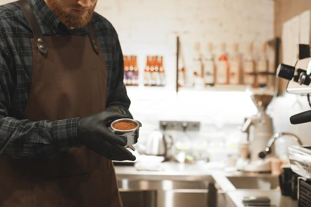 Barista stoi w kawiarni z uchwytem z kawą w rękach.