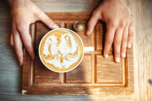 Barista trzyma filiżankę kawy z rysunkiem pianki