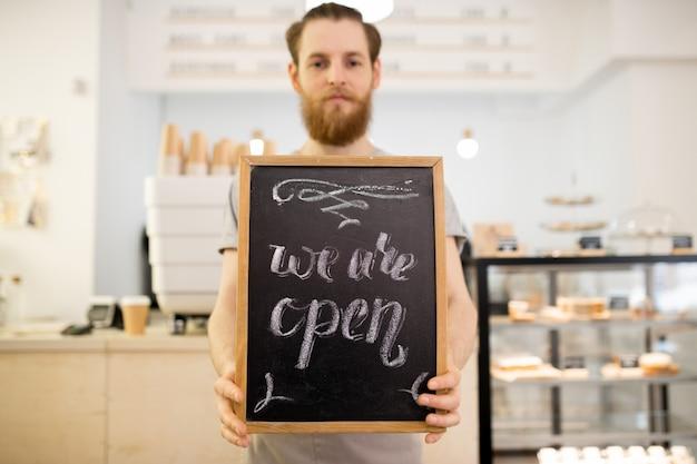 Barista trzyma tablet z napisem we are open