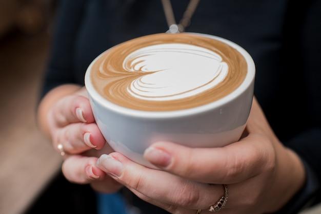 Barista trzymająca w rękach pachnące, świeżo przygotowane cappuccino