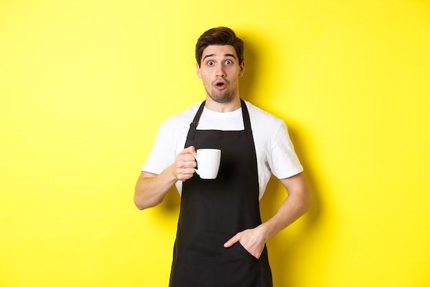Barista trzymający kubek z kawą i wyglądający na zaskoczonego, stojący w czarnym fartuchu kawiarnianym mundurze na tle żółtej ściany