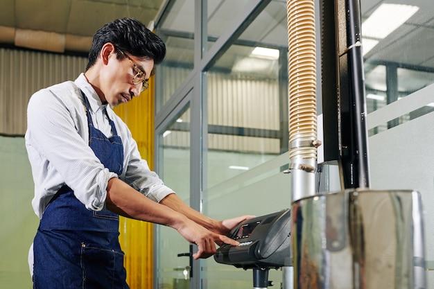 Barista uruchamia maszynę do palenia kawy