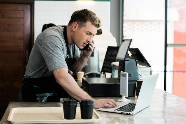 Barista używa laptopa do przyjmowania zamówień od klienta w barze kawowym
