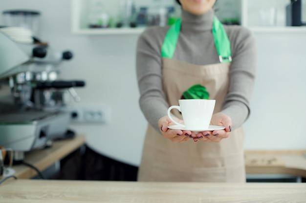 Barista w fartuchu w kawiarni daje świeżo parzoną świeżą kawę klientowi
