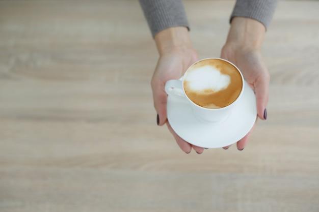 Barista w fartuchu w kawiarni podaje klientowi świeżo parzoną świeżą kawę