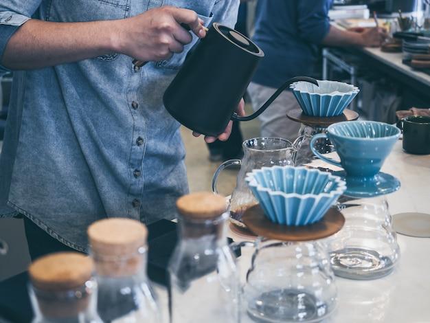 Barista w niebieskiej koszuli wlewający gorącą wodę z czarnego czajnika do zmielonej kawy z filtrem na białym pasku.