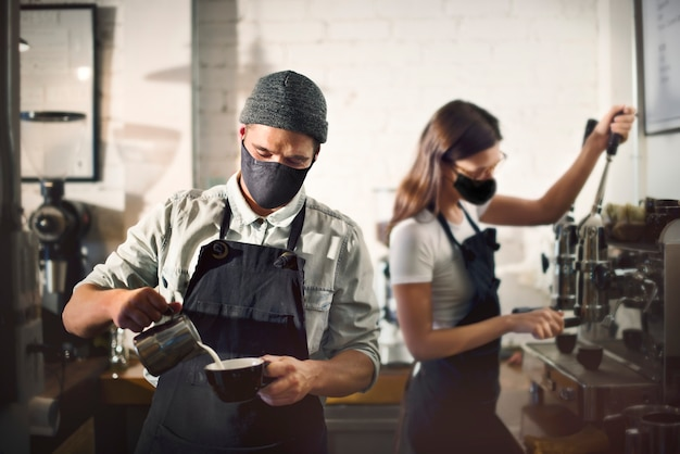 Barista w znaku twarzy w kawiarni w nowej normie