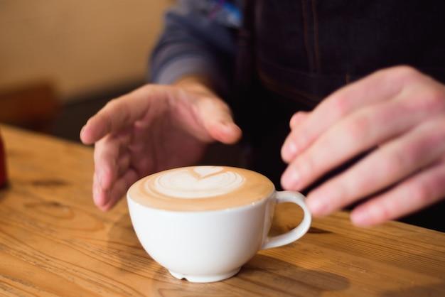 Barista wlewając mleko do filiżanki kawy do robienia latte art.