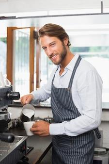 Barista wlewając mleko do kubka kawy