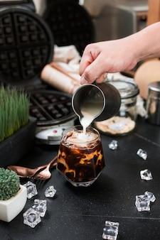 Barista wlewający mleko do szklanki mrożonej kawy
