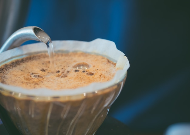 Barista wylewanie gorącej wody na szorstki bańki baniek kawy, proces warzenia domu
