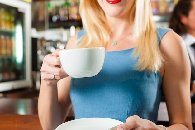 Barista z klientem w jego kawiarni lub kawiarni